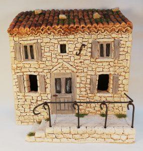 Maison à étage aux volets gris avec terrasse et rambarde
