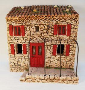 Maison à étage aux volets rouges avec terrasse et pergola